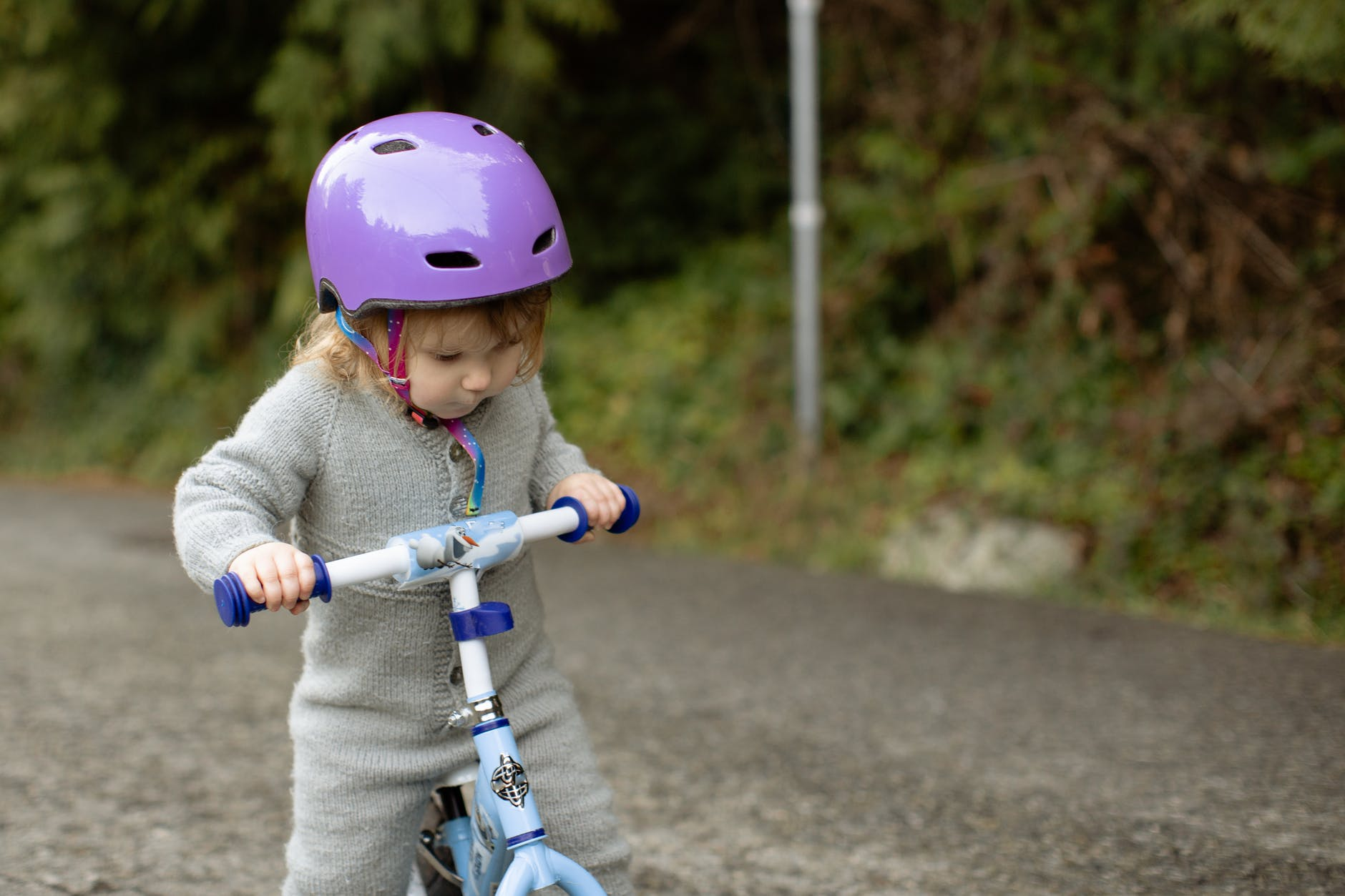 focused little cyclist girl riding runbike at countryside